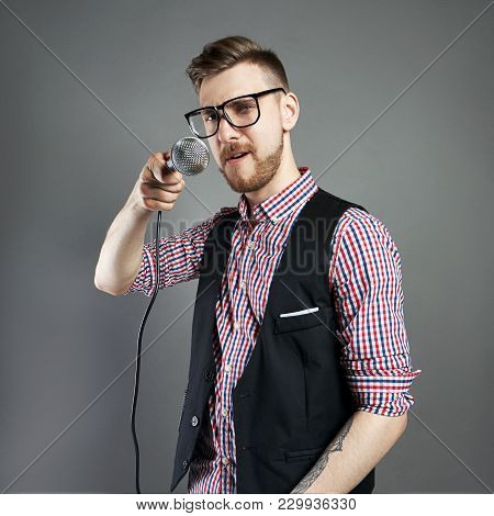 Karaoke Man Sings The Song To Microphone, Singer With Beard On Grey Background. Funny Man In Glasses