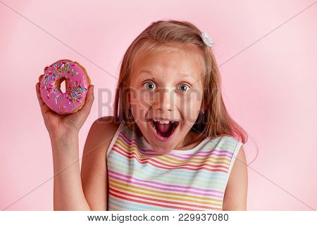 Young Beautiful Happy And Excited Blond Girl 8 Or 9 Years Old Holding Donut On Her Hand Looking Spas