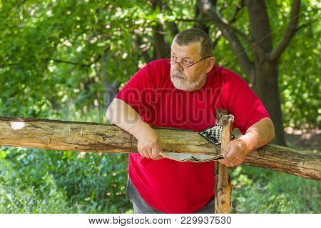 Portrait Of Senior Bearded Man Resting With Newspaper And Mini-chess In Summer Park