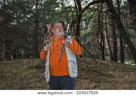 Portrait Of Severe Senior Ranger With Two Rifles Standing In Dark Pine Forest