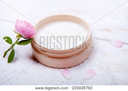 Pot Of Moisturizing Face Cream And Beautiful Flower On A White Wooden Background. Natural Organic Co