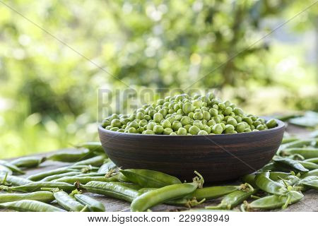 Peeled Green Peas In A Plate On A Wooden Table. It Lies Next To Pea Pods. Horisontal Photo