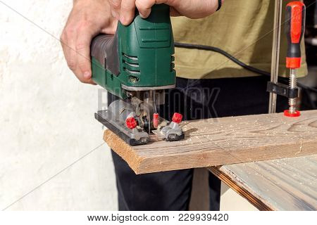 Men's Hands With Electric Jig Saw
