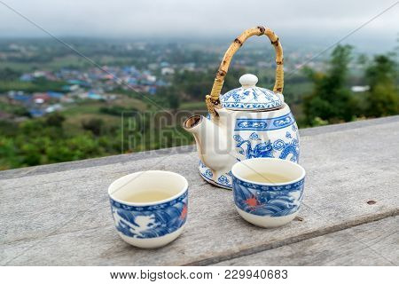 Tea Pot With Cup Set On The Wooden Table In Front Of Mountain View, Traveling In Thailand