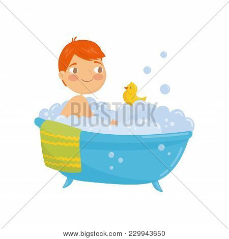 Funny Red-haired Boy Taking Bath With Rubber Duck Toy. Bathtub With Foam Bubbles Inside. Daily Hygie