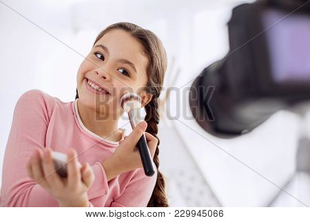 Best Mood. Lively Pre-teen Girl Applying Powder To Her Cheek And Smiling At The Camera While Filming
