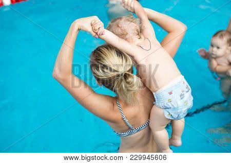 Happy Young Mother Playing With Her Baby In Swimming Pool On Hot Summer Day. Kids Learn To Swim Duri