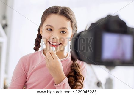 Proper Lip Care. Charming Pretty Pre-teen Girl Putting On Lip Balm On Her Lips And Smiling At The Ca