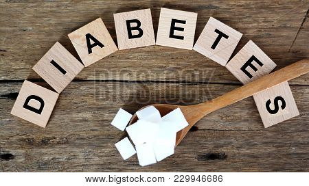 High Blood Sugar Level Concept With Diabetes Word And White Sugar Cubes In Wooden Spoon On Dark Back