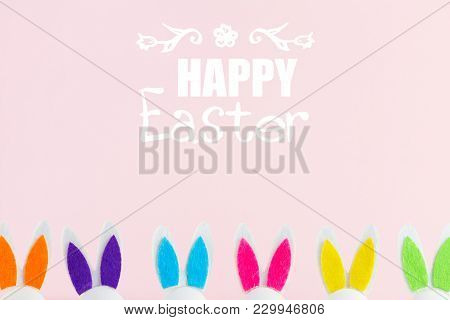 Row Of Funny Easter Bunnies Ears On Pink Background With Happy Easer Greetings