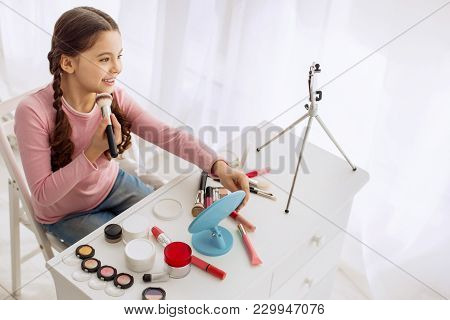 Wannabe Makeup Artist. Charming Upbeat Pre-teen Girl Posing For The Camera And Reviewing Makeup Prod
