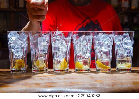cubes of ice in glass with slice of lemon on bar. cocktail