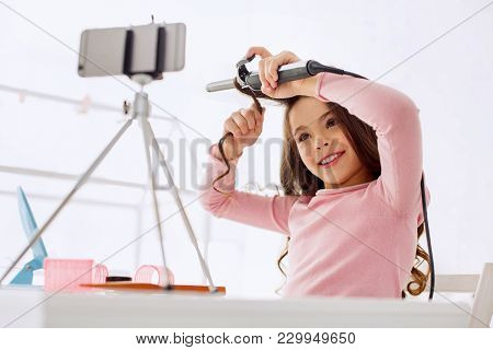 Pretty Locks. Adorable Upbeat Pre-teen Girl Sitting At The Table And Curling A Lock Of Her Hair With