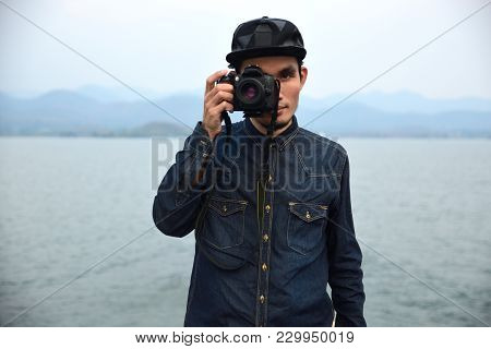 One Man Travel Around The World With One Camera,man Holding Camera On Hand And Standing At Sea,man T