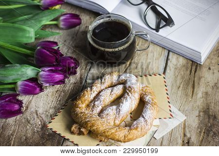 Still Life With Tulips, A Book, Coffee And Pretzel On The Old Wooden Background
