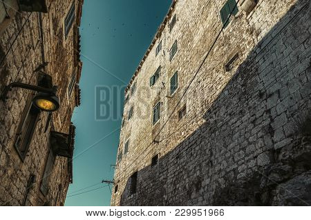 Photo Of Narrow Street (from Down) In Sibenik (croatia) With Flock Of Birds Above The Walls. Histori