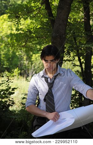 young businessman on nature. development of plans