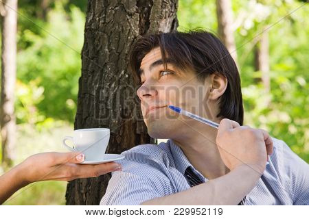 A young guy in the nature is drinking coffee.