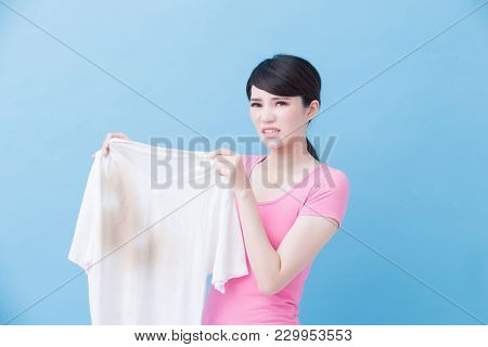 Woman Feel Upset With Dirty Shirt On The Blue Background