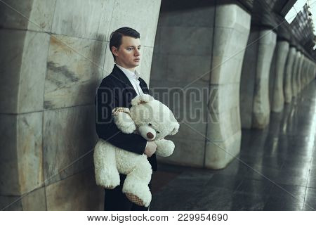 Sad Man Holds A Toy In The Hands Of A Bear.