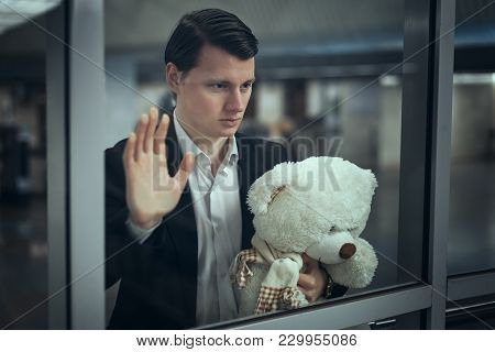 Young Man Looks Out The Window And Waits For A Meeting. He Has A Teddy Bear In His Hands