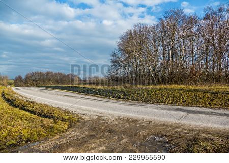 Curve Road In Autumn With Green Meadow And Blue Cloudy Sky And Sun. Empty Curved Road At Sunny Day.