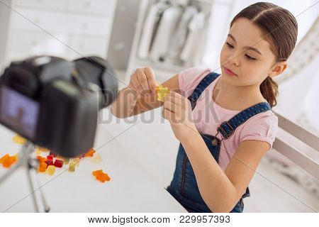 Best Candy. Pleasant Upbeat Girl Stretching One Of The Gummy Bears While Recording A Video Blog And