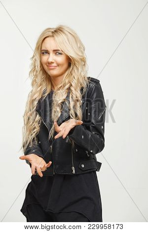Isolated Shot Of Female Portrait With Blond Hair Demonstrates Arrogance. Young Woman Puts Her Hands