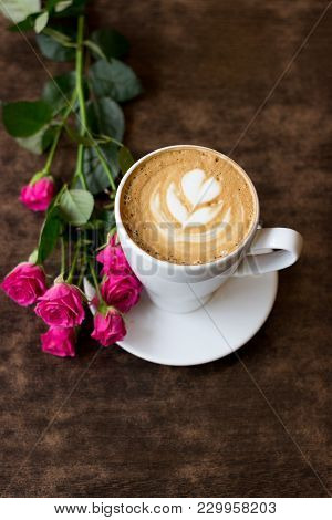 A Fresh Morning Cappuccino In A White Cup With A Heart Of Foam, Stands On A Wooden Table, Near It Li