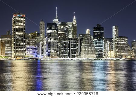 New York City Skyline Reflected In East River At Night, Usa.