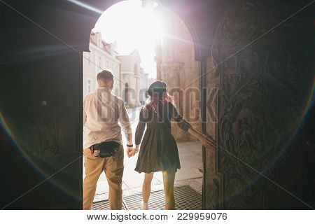 Back View Of Stylish Couple Holding Hands And Walking In Old City With Backlit, Wroclaw, Poland