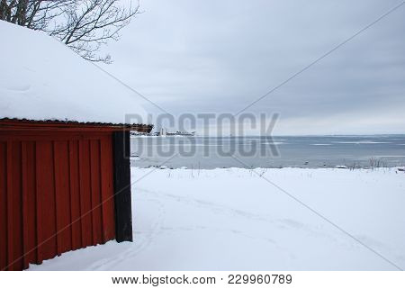 Part Of A Red Cabin By An Ice Covered Bay At The Island Oland In Sweden