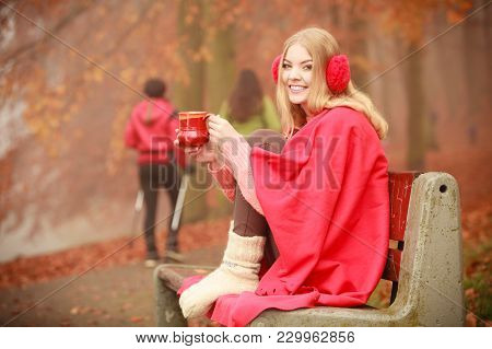 Happiness Carefree And Fall Concept. Young Happy Woman Relaxing In Autumn Park On Bench Enjoying Hot