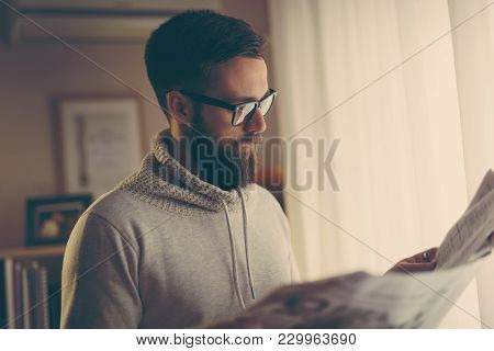Pensive Young Man Reading Newspapers In His Home Library