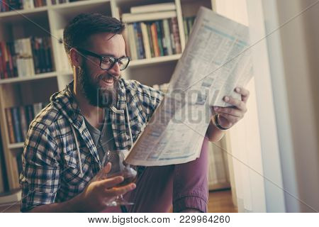 Handsome Young Man Reading Newspapers And Having A Drink In His Home Library