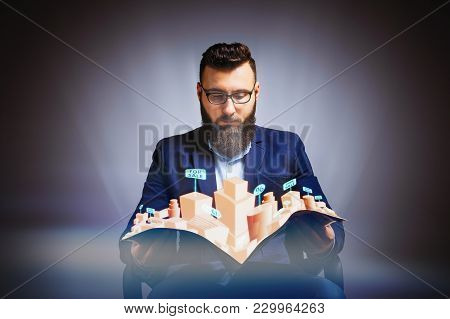 Man Holds A Newspaper In His Hands. Newspaper Has A Hologram With Real Estate For Sale. Concept Of O