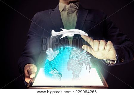 Man Holds A Tablet Pc In His Hands. Tablet Pc Has A Hologram With A Model Of The Earth And Aircraft.