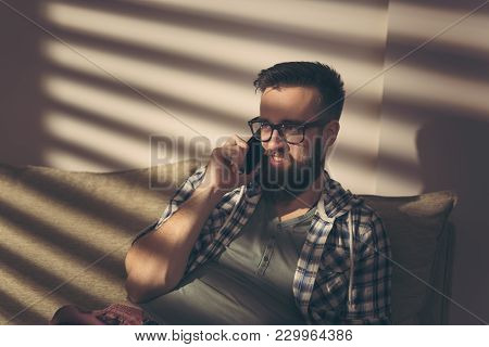 Handsome Young Man Sitting On A Living Room Sofa, Having A Phone Conversation And Relaxing At Home