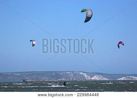 Kitesurfers Riding Boards In Portland Harbour, Dorset