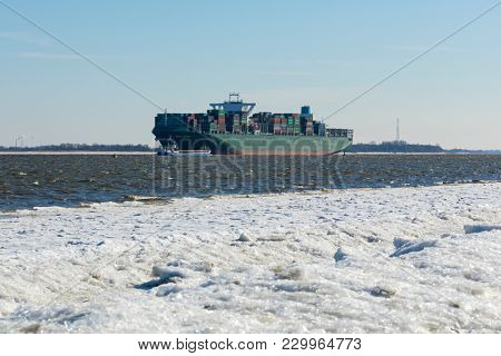 Stade, Germany - March 1, 2018: Container ship TOLEDO TRIUMPH on Elbe river. It is 365 meters long and holds up to 13870 standard containers.