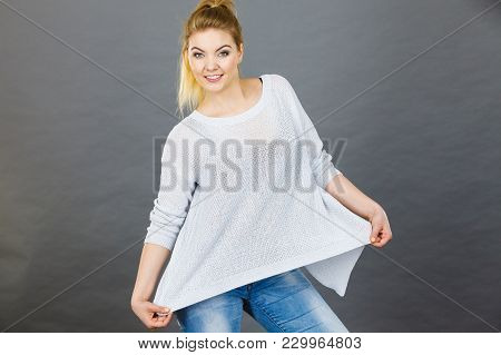 Woman Wearing Too Big Jumper, Not Fitting After Weight Loss. Grey Background