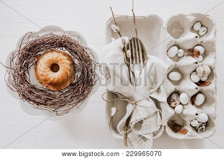Natural Easter Table Decoration With Silverware And Cup Cake In A Wreath On White Wooden Table