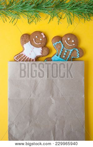 Christmas Gingerbread Mans On Yellow Background. Boy And Girl Peer Out Of The Package. Concept Of Ne