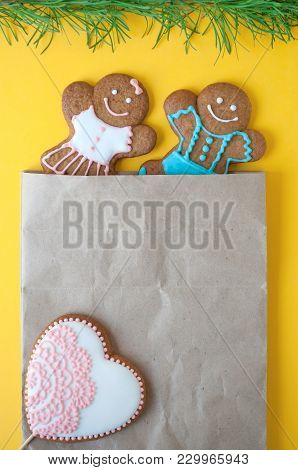 Christmas Gingerbread Mans, Heart On Yellow Background. Boy And Girl Peer Out Of The Package. Concep