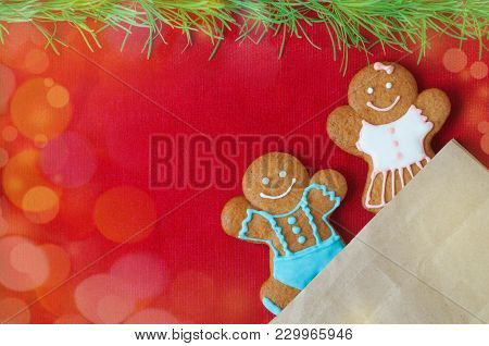 Christmas Gingerbread Mans On Red Background. Boy And Girl Peer Out Of The Package. Concept Of New Y