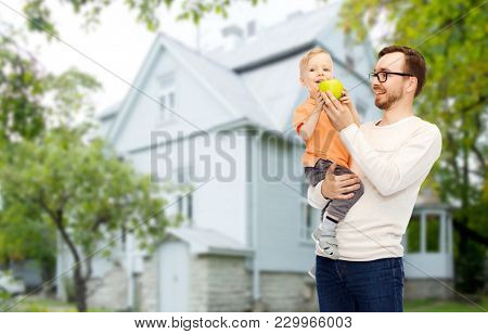 family, childhood, fatherhood, healthy eating and people concept - happy father and and little son with green apple over house background
