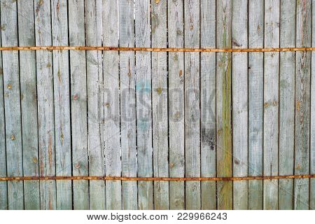 Old Wooden Fence Made Of Narrow Pegs Interlocked With A Twisting Metal Band Over The Entire Fence