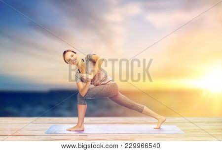 fitness, sport, people and healthy lifestyle concept - woman making yoga low angle lunge pose on pier over sea background