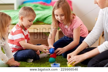 childhood, leisure and people concept - group of happy kids and and mother with modelling clay or slimes at home