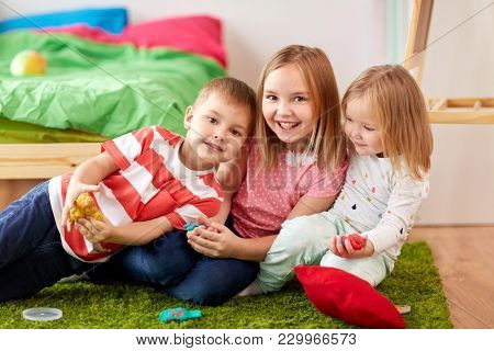 childhood, leisure and people concept - group of kids with modelling clay or slimes at home